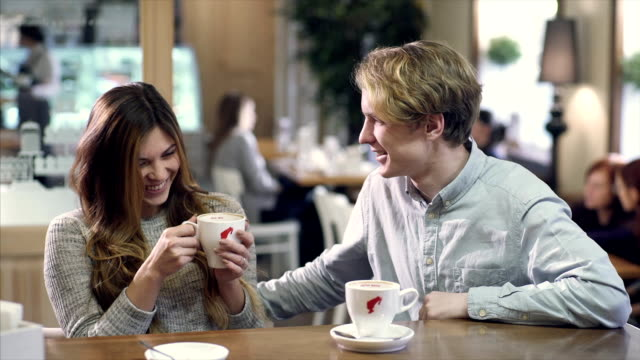 Student couple chatting together in a cafe video