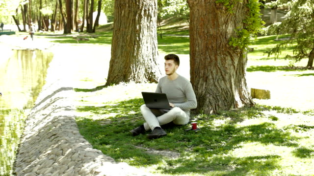 student doing homework on a computer in the park under a tree and drinks coffee video