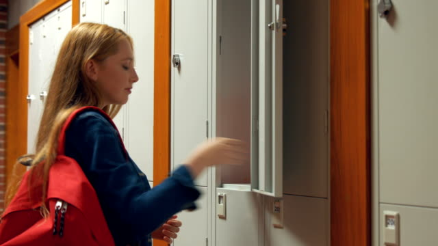 Student gathering her school books from a locker video