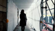 Student girl walking through the white construction corridor. Back view of young woman goes to work across the building video