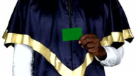 Student holding a green card and shows the thumb. White. Close up video