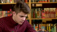 Student  in a library, preparing for Abstracts. Close up video