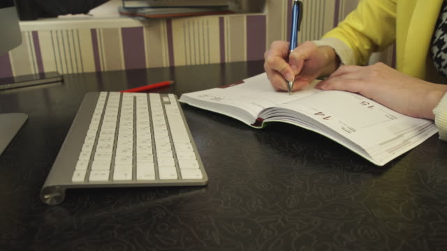 A student in a yellow jacket writing in a notebook video