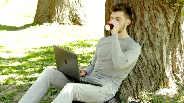 Student invigorates with a cup of coffee and works with laptop video