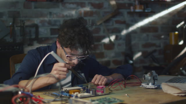 Student is studying electronics and soldering a circuit board in a garage. video