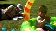 Student man study book and look after infant child sitting in pool video