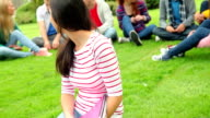Student smiling at camera with friends behind her on grass video