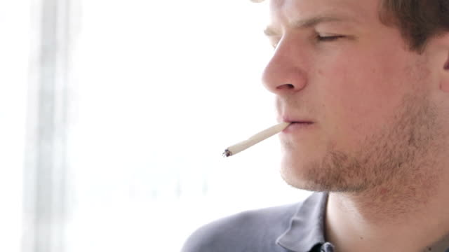 Student smoking hand-rolled cigarette video