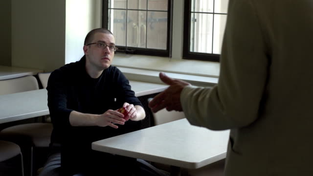 Student talking with professor in classroom video