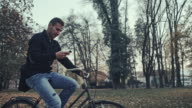 Student typing sms while riding a bicycle through the park video