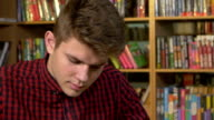Student using his digital tablet in a library, preparing for Abstracts. Close up video