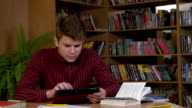 Student using his digital tablet in a library, preparing for Abstracts. Close up, slow motion video