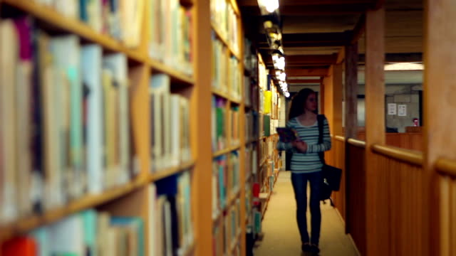 Student walking through the library video