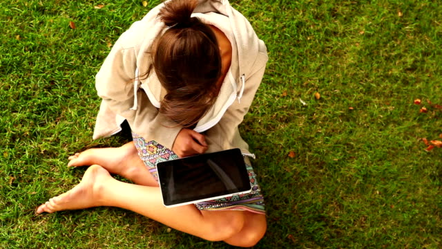 Student working with tablet pc sitting on grass video