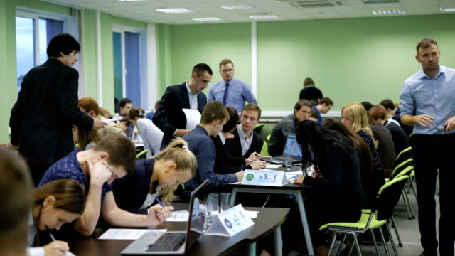 Students complete their task quickly and pass the examination papers. Ends the exam at the university. Large modern classroom video