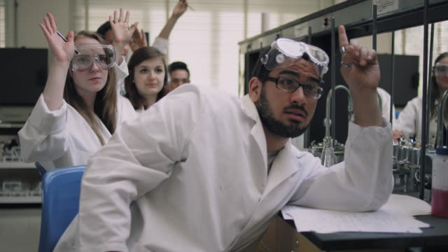 Students in a science lab listen to their professor and raise their hands video