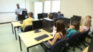 Students in computer lab raise hands video