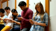 Students leaning against lockers using smartphones video