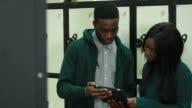 Students looking at digital tablet in university video
