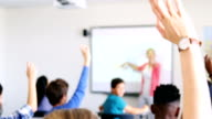 Students raising their hands in classroom video