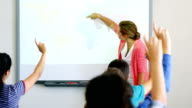 Students raising their hands while teacher teaching them in classroom video