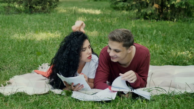 Students read synopses, preparing to exams in park video