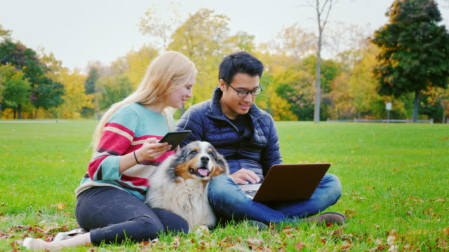 Students relaxing in the park. Asian man uses a laptop woman with tablet sitting nearby video