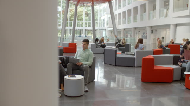 Students socialise in the busy lobby of a modern university video