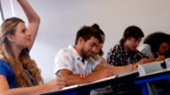 Students taking notes in class video