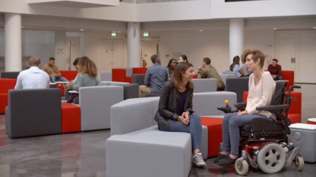 Students talking in a meeting area in a university lobby video