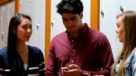 Students using smartphones in locker room video