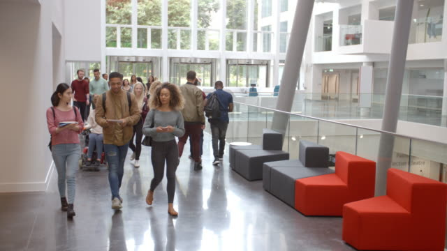 Students walk through the foyer of a modern university video