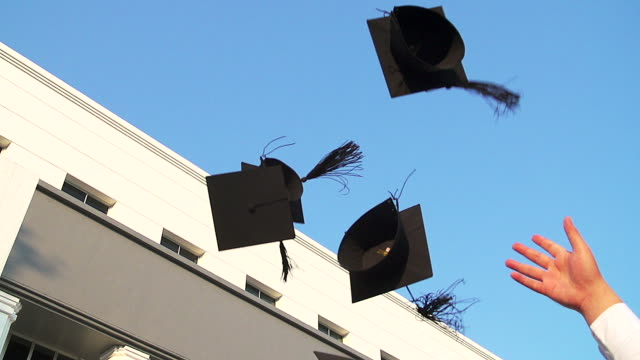 Students with congratulations throwing graduation hats in the air celebrating. video