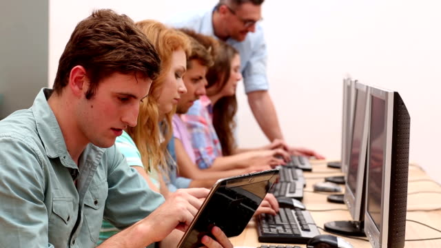 Students working in computer room with lecturer video