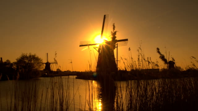 Stunning authentic old windmill on the river bank at beautiful golden evening video