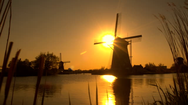 Stunning authentic old windmill on the river bank at beautiful golden morning video