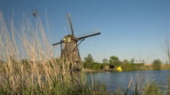 CLOSE UP: Stunning authentic vintage windmill on the river bank turning blades video