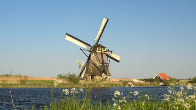 CLOSE UP: Stunning traditional antique wooden windmill next to beautiful river video