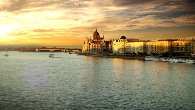 A stunning view of the Hungarian Parliament Building over the Danube River at sunset video