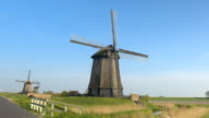 CLOSE UP: Stunning wooden windmill heritage next to small road on sunny day video