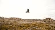 SLO MO Stunt biker jumping over dirt ramp video