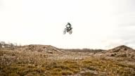 SLO MO Stunt dirt biker jumping over dirt ramp video