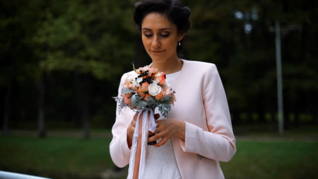 stylish bride with a beautiful bouquet of flowers in the park video
