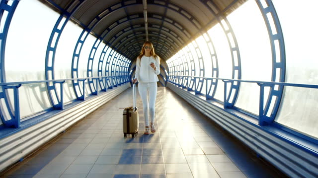 Stylish business woman dressed in white comes with travel bag on the tunnel of glass or transition. Light of the setting sun, enjoys a telephone video