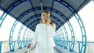 Stylish business woman in white suit goes through the tunnel, or the transition from the glass. Lucky bag on wheels, holding a mobile phone video