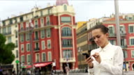 Stylish businesswoman sending a text outdoors on urban background video
