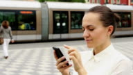 Stylish businesswoman with mobile phone on urban background video