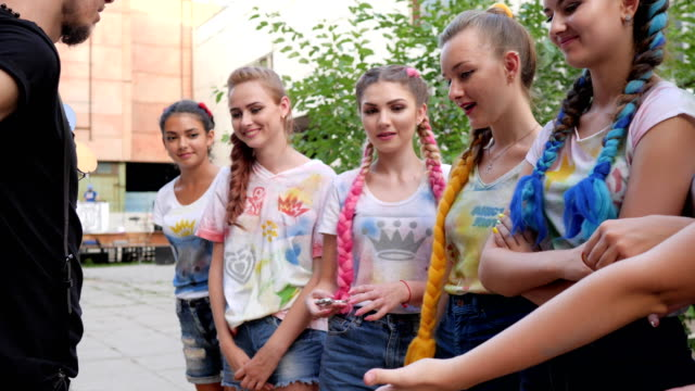 stylish girls standing on street with trendy braids with kanekalon, adolescents with bright hair at background of graffiti video