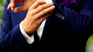 Stylish groom in blue luxury suit wearing cufflinks close up video