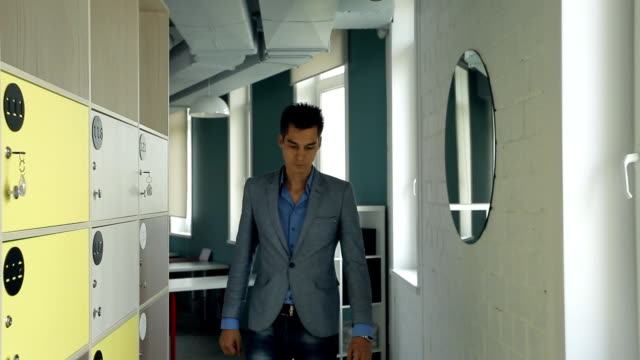 Stylish man in a jacket walks past a mirror and adjusts her shirt in office video